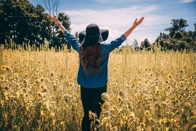 Grateful women on sunflower field